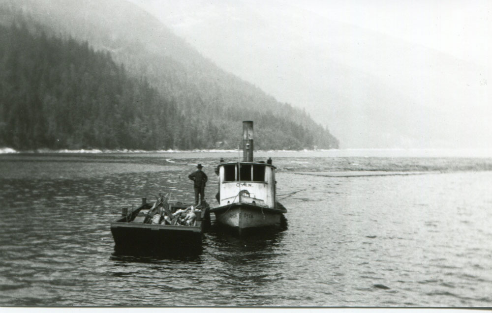 """Tugboat """"Oyen"""" towing the biggest log boom to Slocan for Jenning's Sawmill, circa 1927"""
