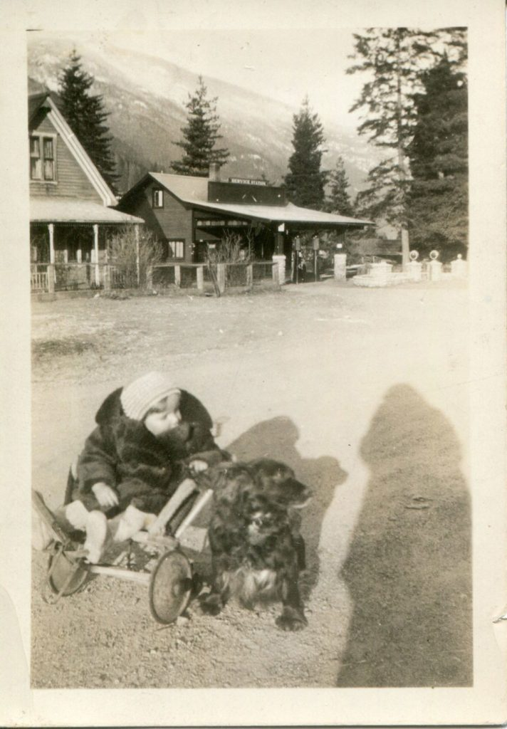 """Jim Barker with dog """"Laddie"""", building in the background WI building on left, Greenlight Service Station on the right, circa 1940"""